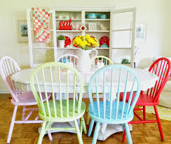 pastel and bright colored wooden kitchen chairs with white oval table in a dining room with parquet flooring