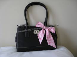 Classically styled handbag with removable pink   white Coach silk bow. Made  of beautiful black calfskin leather. Back of bag has embossed Coach logo.