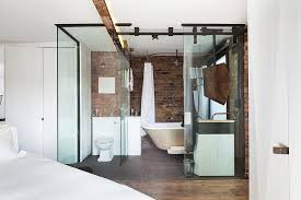 modern glass cubicle shaped bathroom with walk in shower and bedroom view