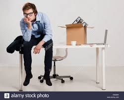 young man sitting on the desk after being fired stock photo stock photo young man sitting on the desk after being fired