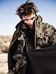 broody in another snap pattinson hides underneath a matador style cape worn over