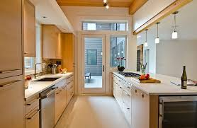 Mini wine racks hold up ceiling skimming shelves, a glass mixing bowl doubles as a fresh egg holder, and a water jug sidelines as cooking utensil storage. Galley Kitchen Design Ideas That Excel