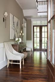 the gray walls are a perfect balance to the white trim and absolutely gorgeous wood floors creamy leather covers the accent chairs the flank the wooden