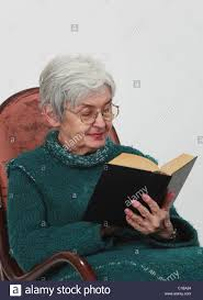 portrait of an old woman reading a black book against a grey background