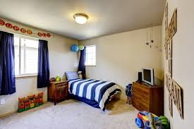 Decorated Boys Room Interior With Beige Walls, Blue Curtains, Striped Blue  Bedding And TV