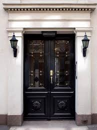 perfectly intricate black door with gold accents and pitch black sconces on either side