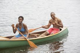 couple canoeing with two wooden boat oars
