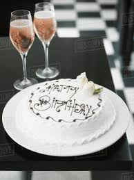 A White Birthday Cake And Rose Champagne Stock Photo Dissolve