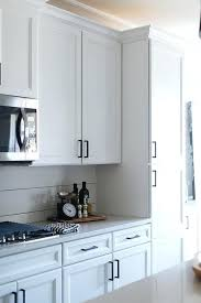 off white shaker kitchen cabinets white shaker kitchen cabinets accented with oil rubbed bronze pulls are finished with an off white quartz fixed against a