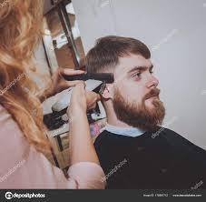 若い男の美容師が髪型を作るマスター カット髪と男性のひげ ストック