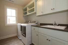pale green laundry room cabinets with dark gray countertops