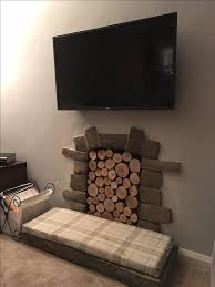 the silver birch logs have been used to fill the alcove in the old fireplace and
