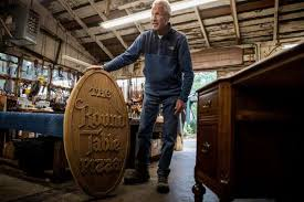 1of10tom kieninger owner of the barn wood in menlo park shows off the original 1955 wooden round table pizza sign which was brought into the