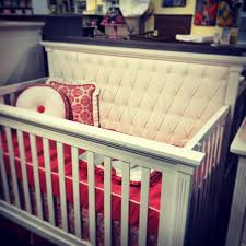Coral Damask crib bedding on display in a white leather tufted