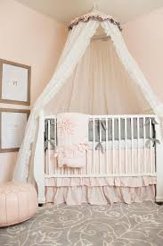 gorgeous pink and gray nursery features two wood framed typography prints mounted on light pink walls highlighting a white tulle canopy hanging over a white
