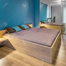 Geräumiges Blaues Schlafzimmer Mit Großem Holzbett Und Gespiegelten