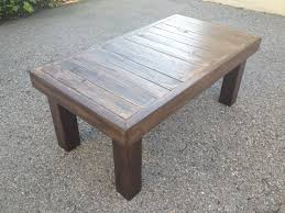 simple dark brown finished rectangular reclaimed wood coffee table with four legs on concrete pavers as outdoor backyard garden furnishings ideas