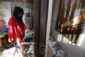 a painter who has lost a right arm works in her studio