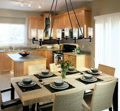 black iron rectangle dining room chandelier over wicker rattan dining table top and dining chairs