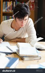 portrait serious student writing essay library stock photo  portrait of a serious student writing an essay in a library