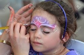 little age 5 6 getting her face painted with a crown like a princes