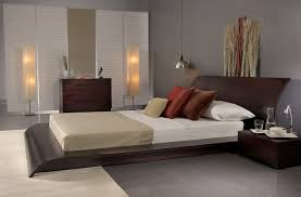 black wooden low bed frame with curving head board combined with white cream bedding set plus brown pillows