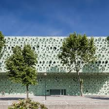 Perforated green cladding wraps university science institute by Cludio  Vilarinho