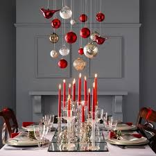 Glass ornaments in silver and red hang above this Christmas table with a  centerpiece of red candles in clear glass candlesticks atop mirrored trays.