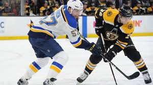 david perron of the st louis blues and jake debrusk of the boston bruins battle