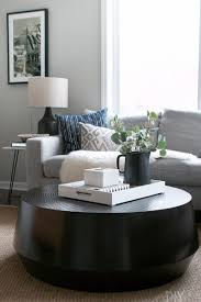 a black round coffee table complements the straight lines of a gray sectional in this family