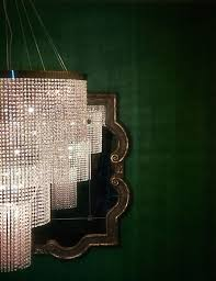 emerald wallpaper behind glamorous crystal chandelier fashiongonerogue