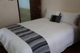 a bed or beds in a room at century gardens