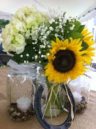Burlap, sunflowers and horseshoes. Elegant, country centerpieces!
