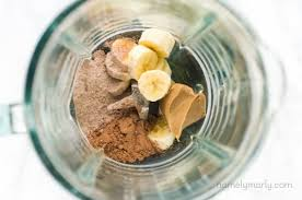 looking down into a blender there are banana slices peanut er cocoa powder