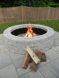 cozy unilock pavers with exciting fire pit kit and wooden fence for exciting backyard design