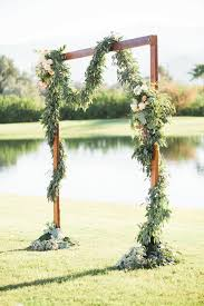 simple wooden ceremony arch with lots of greenery