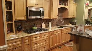 A dark layered stone backsplash adds texture and contemporary style to this  light wood and granite