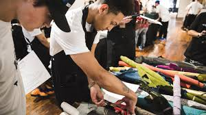 two guys hard at work cutting fabric for their nike shoe