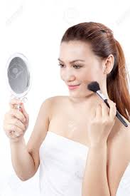 woman holding mirror. asian woman applying make up on her face using a brush while holding mirror r