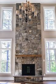 family room two story stone fireplace rustic wood mantle flanked by windows