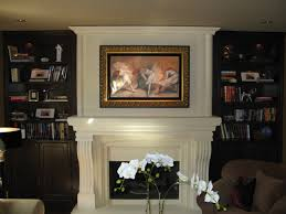 interior white carving fireplace mantel with shelf and picture above between black wooden books shelves