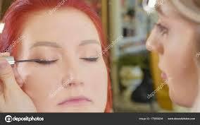 make up artist applying makeup to models eye close up view stock