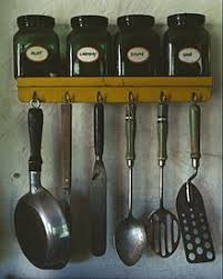 kitchen utensil: various kitchen utensils at top a spice rack with jars of mint caraway
