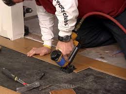 using tool to install hardwood floor pieces