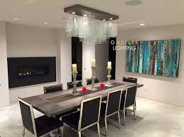 a beautiful modern clear glass chandelier over a dining table designed by galilee lighting