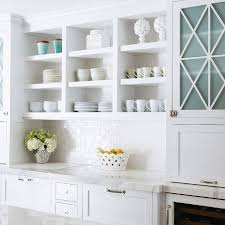 white kitchen features open shelving filled with pottery over a a white subway tiled backsplash and white cabinets next to blue glass cabinet doors