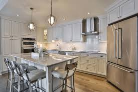 white kitchen design with white cupboards stainless steel appliances hardwood floors and a