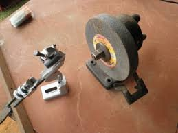 grinder wheel for drill. a highly geared-up hand crank powers this grinding wheel. you can also see the drill bit sharpening attachment. grinder wheel for
