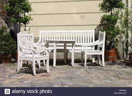 wooden outdoor furniture painted. White Painted Wooden Patio Furniture Outdoor In A Paved Angle Of Garden - Stock Image I