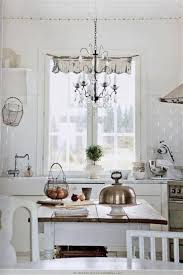 shabby chic white kitchen with chandelier lighting fixtures quirky kitchen clocks quirky kitchen signs